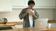 MS OF A MAN HAVING BREAKFAST USING A LAPTOP Stock Footage
