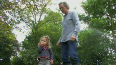 LS PAN OF A FATHER LIFTING AND CARRYING HIS DAUGHTER ON HIS SHOULDERS Stock Footage