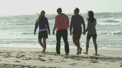 FOCUS SHIFT LS PAN OF FRIENDS WALKING ALONG A BEACH Stock Footage