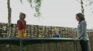 LS PAN OF A MOTHER WATCHING HER DAUGHTERS JUMPING ON A TRAMPOLINE Stock Footage