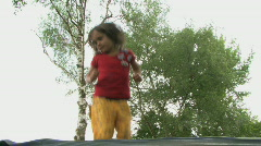 MS PAN OF A GIRL JUMPING ON A TRAMPOLINE Stock Footage