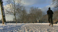 LS OF JOGGERS RUNNING IN THE SNOW IN VICTORIA PARK LONDON Stock Footage