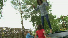 LS PAN OF A MOTHER JUMPING ON A TRAMPOLINE Stock Footage