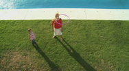 WS OF A MOTHER AND DAUGHTER PLAYING WITH A PLASTIC HOOP Stock Footage