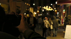 A photographer takes picture of a crowded street at night Stock Footage