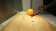 Slicing an orange in half Stock Footage