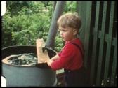 Boy plashing in water barrel (vintage 8 mm amateur film) Stock Footage
