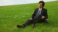 Handsome man in suit get lying on green grass and lift up legs Stock Footage