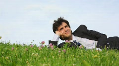 Happy handsome man lying on green grass and legs of passerby Stock Footage