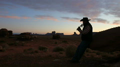 Navajo Man Playing Traditional Instrument in Silhouette at Sunrise in Monument V - stock footage