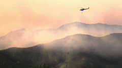Helicopter going by camera put out fire Stock Footage