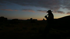 Silhouette of Navajo Man Wearing Cowboy Hat Playing Tribal Instrument at Sunrise Stock Footage