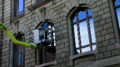 Man cleaning window on crane Stock Footage