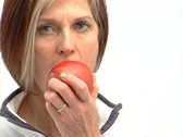Stock Video Footage of Mature healthy female eating red apple
