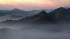 Smokey sunset pan left from mountains to valley Stock Footage