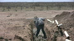 Worker Leveling Out Stones in Drainfield for Septic Stock Footage