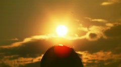 Silhouettes of a head and hands of man against sun Stock Footage