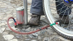 Boy's foot on air-pump, pumping bicycle wheel Stock Footage