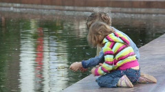 Boy and girl playing fishing at city pond Stock Footage