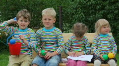 4 kids sitting on bench and throwing balls Stock Footage