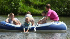 Family with 4 kids in rubber boat, rowing Stock Footage