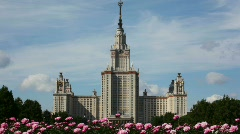 Flowers moving with wind in front of Lomonosov Moscow State University Stock Footage