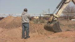 Backhoe Working with Man Watching Stock Footage