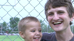 Young Male and Baby Boy by fence - stock footage