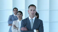 Businessman leading his team with folded arms - stock footage