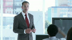 Businessman reporting sales figures to his team Stock Footage