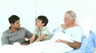 Dad and son visiting a grandfather recovering in hospital Stock Footage