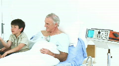 Panorama of grandson and father visiting a senior man in hospital - stock footage