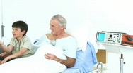 Panorama of grandson and father visiting a senior man in hospital Stock Footage