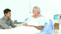 Grandson and father visiting a senior man recovering in hospital - stock footage