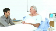 Grandson and father visiting a senior man recovering in hospital Stock Footage
