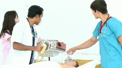 Doctors resuscitating a little boy with a defibrillator Stock Footage