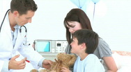 Doctor playing with a little boy recovering in hospital and his teddy bear Stock Footage