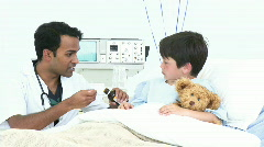 Doctor giving a little boy syrup in hospital Stock Footage