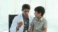 Doctor giving a little patient syrup in surgery's office Stock Footage