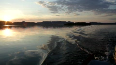 POV shot from a boat crossing a bay at sunset Stock Footage