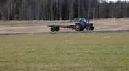 A tractor drives on a country road. It passes farm houses and meadows. Stock Footage