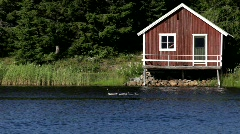 A familiy of Canada geese swims in front of a boathouse. - stock footage