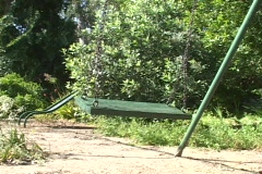 An abandoned swing sways on an empty playground. Stock Footage
