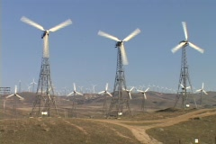Large windmills spin at a wind-farm. Stock Footage