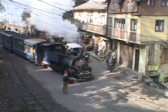 A steam train passes the city of Darjeeling, India. Stock Footage