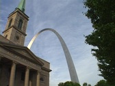 Stock Video Footage of The St. Louis arch rises above an old church.