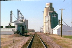 A grain silo stands along a railroad track. Stock Footage