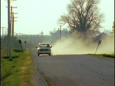 Stock Video Footage of A pickup truck drives down a dirt road.