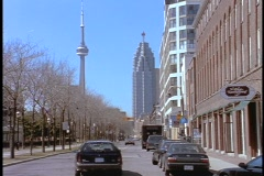 Cars drive down a street in Toronto in front of the CN Tower. Stock Footage