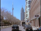 Stock Video Footage of Cars drive down a street in Toronto in front of the CN Tower.